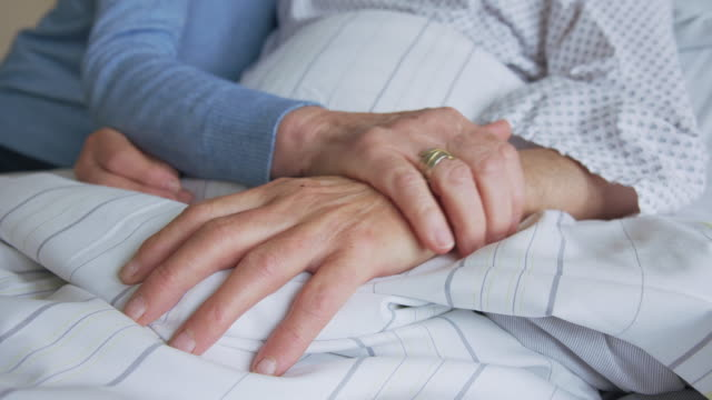Senior woman comforting hospitalized husband