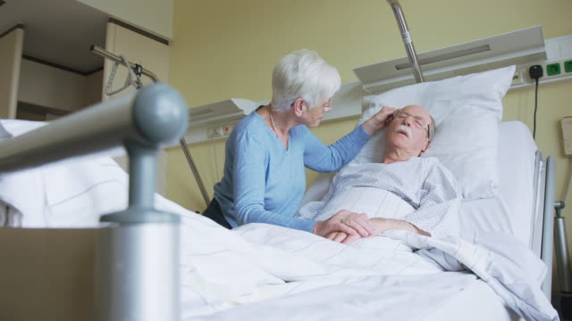 senior woman comforting restless husband in hospital bed - morte video stock e b–roll