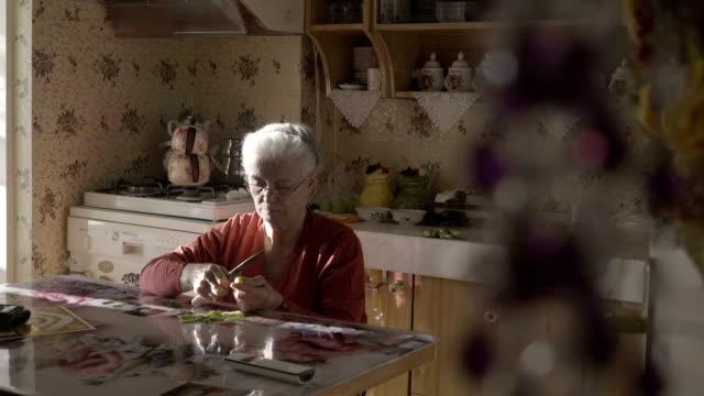 senior woman cooking a healthy meal - samotność filmów i materiałów b-roll