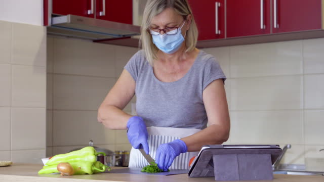 Bидео Senior woman cooking at home during pandemic crisis