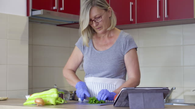 Senior woman cooking at home during pandemic crisis