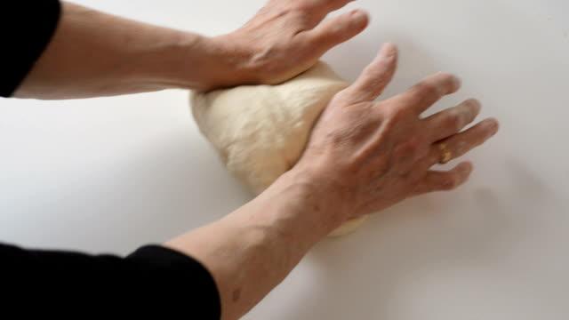 Senior woman cooking. Kneading dough
