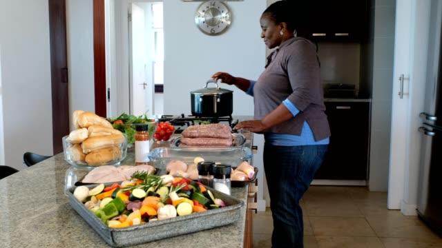 vídeos de stock e filmes b-roll de senior woman cooks in her kicthen - cooker happy