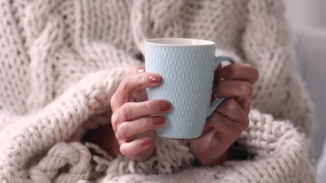 senior woman covered with plaid drinking tea, close up view - время дня стоковые видео и кадры b-roll
