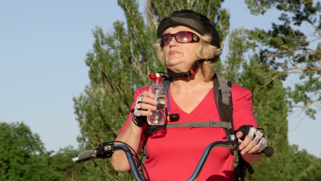 Senior woman cyclist on a bicycle drinking water from bottle video