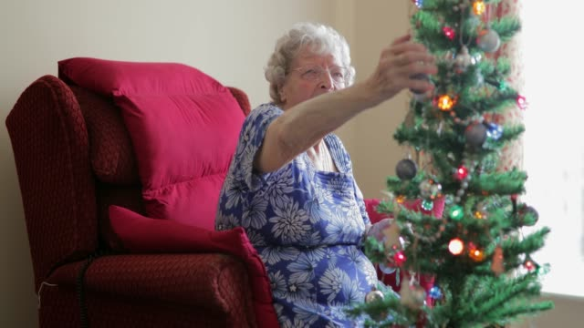 Senior Woman Decorating a Christmas Tree Senior woman decorating a Christmas Tree with a young man helping her. She is in her living room in assisted accommodation christmas fun stock videos & royalty-free footage