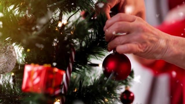 donna anziana decorare albero di natale - decorare video stock e b–roll