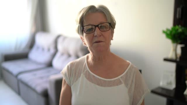 senior kvinna gör ett videosamtal hemma - pov av kameran - saknad känsla bildbanksvideor och videomaterial från bakom kulisserna