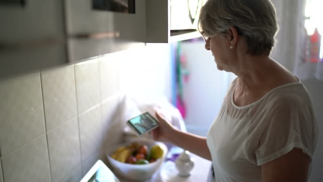 Senior woman doing a video call using mobile phone at home