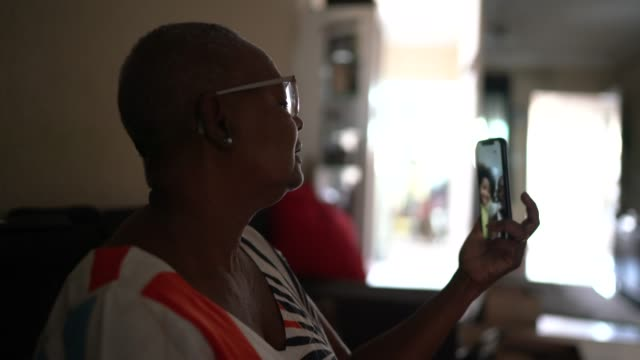 donna anziana che fa una videochiamata con il cellulare a casa - nonna video stock e b–roll