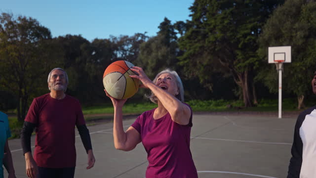 donna anziana che dribbling basket con gruppo di anziani all'aperto campo - anziani attivi video stock e b–roll