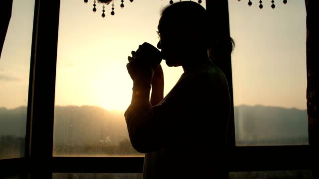 vídeos de stock, filmes e b-roll de mulher sênior que bebe uma chávena de café - café bebida