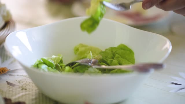 Senior woman eating lettuce salad Senior woman eating her breakfast, pitching salad with her fork from a bowl salad bowl stock videos & royalty-free footage