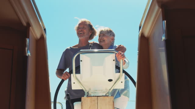 Senior woman embracing man driving yacht in summer
