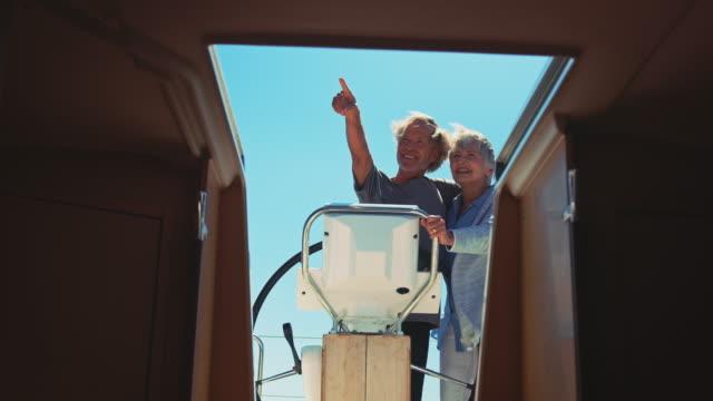 Senior woman embracing man steering yacht
