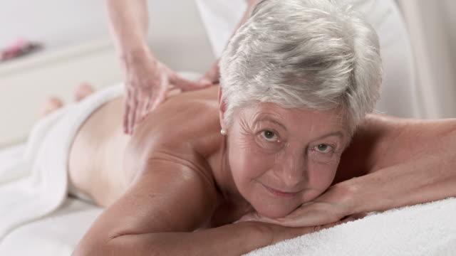 vídeos y material grabado en eventos de stock de hd: mujer mayor disfrutando de un masaje de espalda - tratamiento de spa