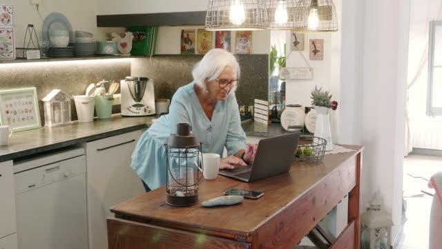 Senior Woman Enjoying Coffee in Kitchen with Laptop