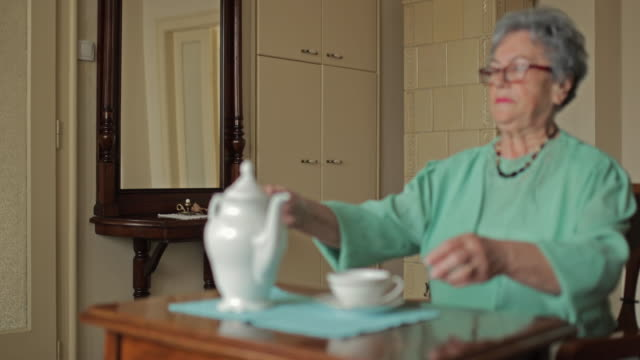 Senior woman enjoying in tea time at home and looking at camera. video