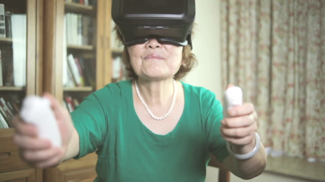 ältere frau genießen vr im innenbereich - bizarr stock-videos und b-roll-filmmaterial