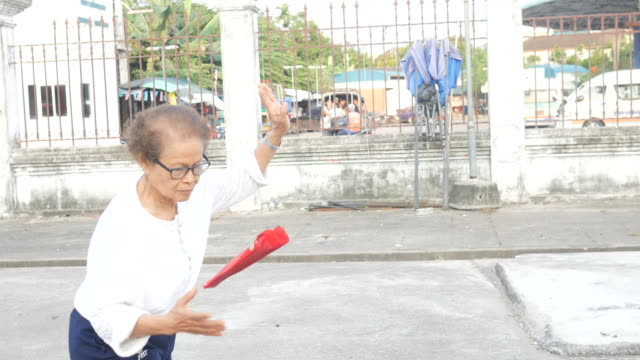 senior woman exercise Chinese hand fan dance at car park video