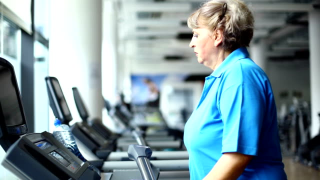 Senior woman exercising on a treadmill. video