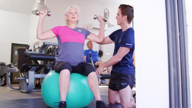 vídeos de stock, filmes e b-roll de mulher sênior exercício na bola suíça com pesos sendo incentivados por personal trainer no ginásio - personal trainer