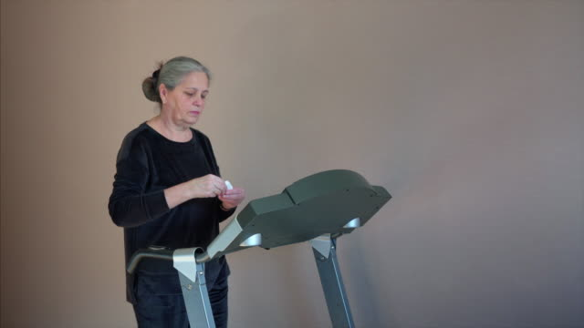 senior woman exercising on treadmill at home wearing wireless earphones - runner rehab gym video stock e b–roll