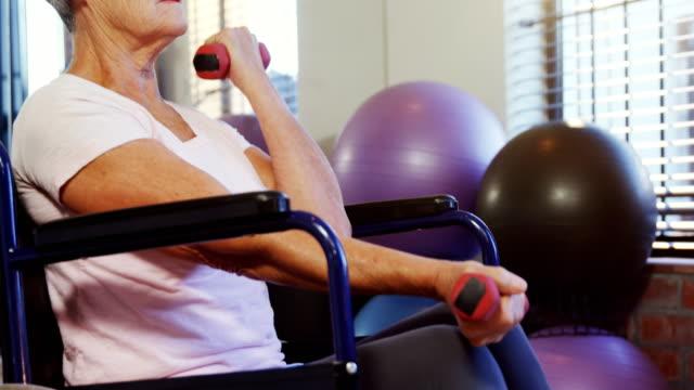Senior woman exercising with dumbbells 4k video
