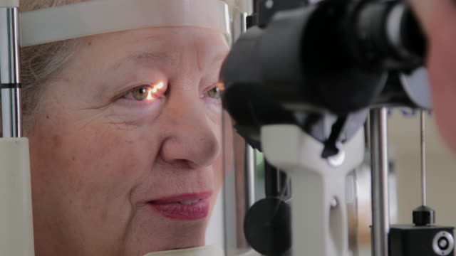 Senior woman eye examination Ophthalmologist examining eye of senior women with aid of a slit lamp. ophthalmologist stock videos & royalty-free footage