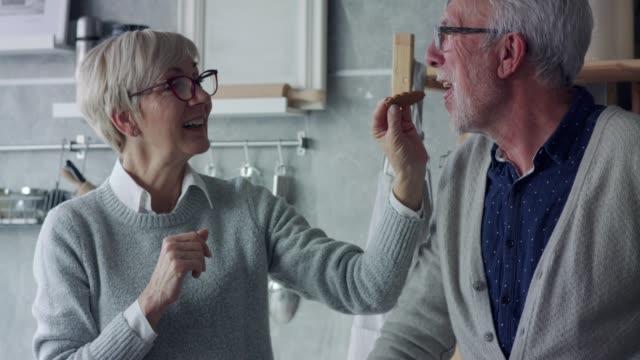 senior kvinna utfodring hennes man en pepparkakor cookie - pepparkaka bildbanksvideor och videomaterial från bakom kulisserna