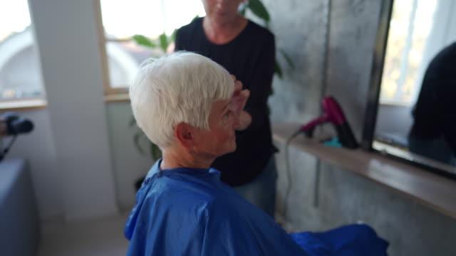 senior woman feeling comfortable at beauty salon - siwe włosy filmów i materiałów b-roll