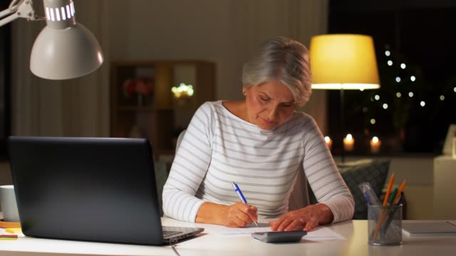senior woman filling tax form at home in evening - vídeo