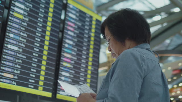 Senior woman finding flight time at Airport