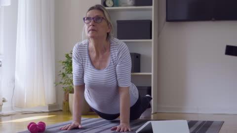 vidéos et rushes de femme aînée suivant tutoriel en ligne et l'exercice à la maison pendant l'isolement pour covid - 19 à la maison - relaxation