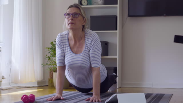 Bидео Senior woman following tutorial online and exercise at home during isolation for Covid - 19 at home