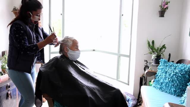 seniorin bekommt einen haarschnitt zu hause während covid-19 pandemie tragen gesichtsmaske - friseur lockdown stock-videos und b-roll-filmmaterial