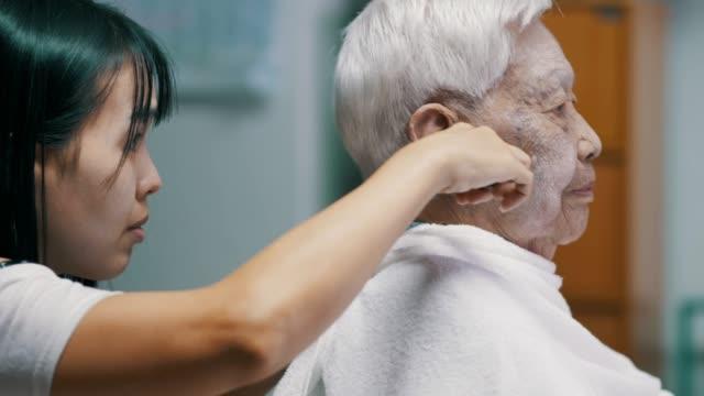 seniorin bekommt einen haarschnitt von enkelin zu hause während coronavirus quarantäne - friseur lockdown stock-videos und b-roll-filmmaterial