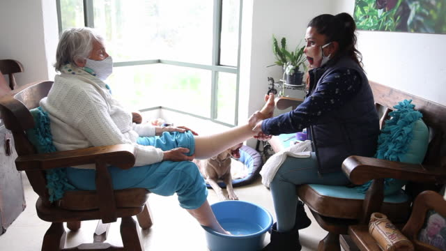 senior woman getting a pedicure at home during covid-19 pandemic wearing face mask - pedicure filmów i materiałów b-roll