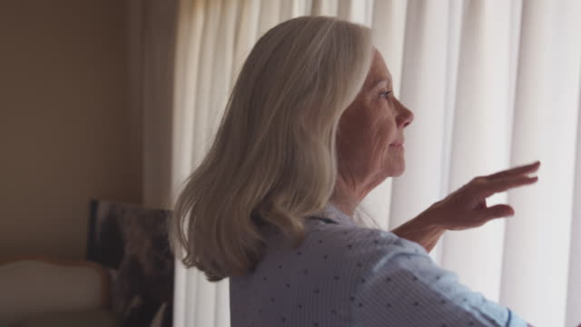 vídeos de stock e filmes b-roll de senior woman getting out of bed and opening bedroom curtains - acordar