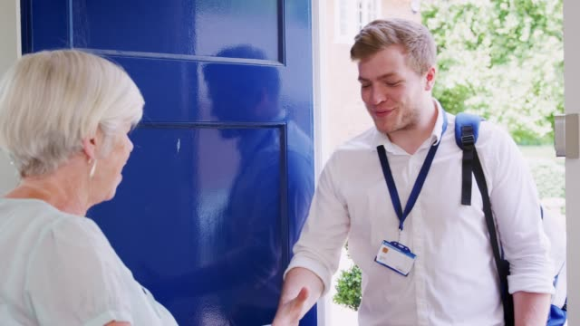 Senior woman greeting male care worker making home visit Senior woman greeting male care worker making home visit sociology stock videos & royalty-free footage
