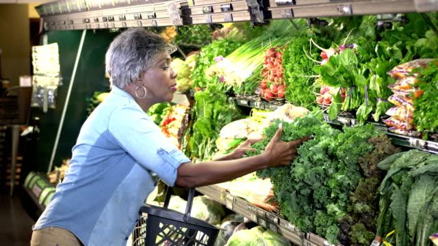 anziana donna spesa in produzione corridoio - mercato frutta donna video stock e b–roll