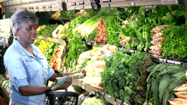 Senior woman grocery shopping in produce aisle