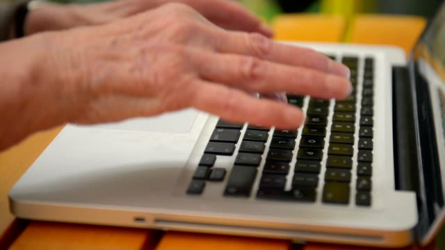 Senior woman hands typing on computer keyboard video