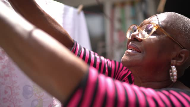 Senior woman hanging clothes in the clothesline to dry at home Senior woman hanging clothes in the clothesline to dry at home hanging stock videos & royalty-free footage