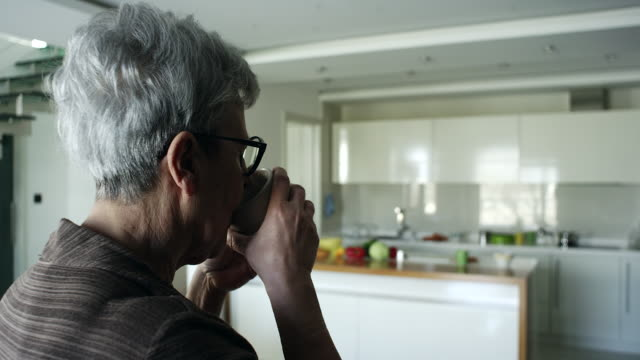 Senior woman having a cup of coffee at home video