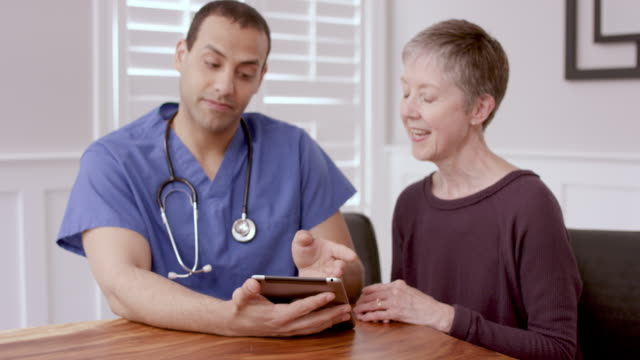 Senior Woman Having An At Home Medical Appointment With Her Mail Nurse A senior caucasian woman is sitting at home at her dining table with her ethnic male nurse. They are having a discussion and appear to be content. nutritionist stock videos & royalty-free footage