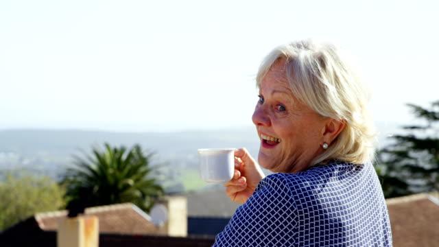 senior woman having coffee in balcony 4k - 60 69 anni video stock e b–roll