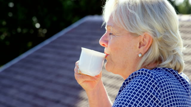 senior woman having coffee on terrace 4k - 60 69 anni video stock e b–roll