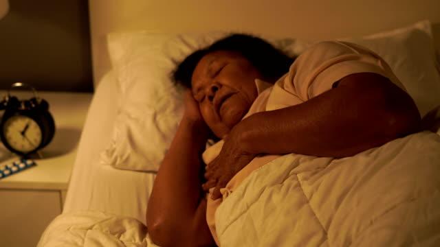 senior woman having heart problem in a bed at night - serce człowieka filmów i materiałów b-roll