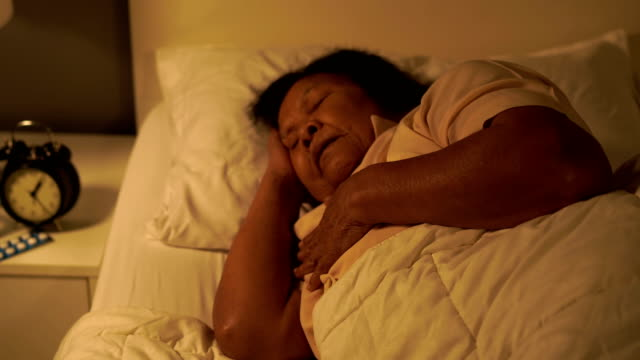 vídeos de stock e filmes b-roll de senior woman having heart problem in a bed at night - coração humano
